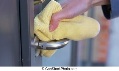 hand cleaning doorhandle with detergent and rag - hygiene, ...