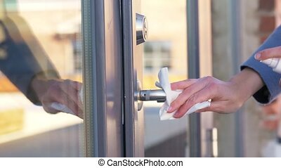 hand cleaning doorhandle with disinfectant spray - hygiene, ...