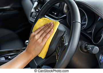 hand cleaning steering wheel of car with microfiber cloth