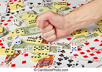 Hand clenched in a fist and playing cards