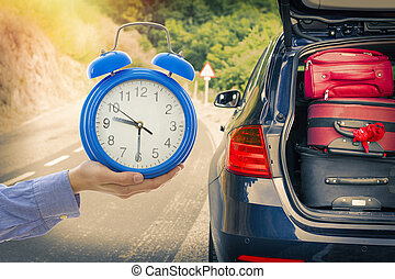 hand-clock and car with suitcases, travel time concept