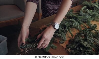 Hand closeup. Florist at work: woman hands making christmas decorations garland of fir Nobilis. Happy new year dinner feast