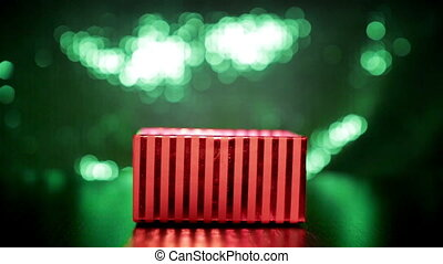 Hand closing red gift box on green background