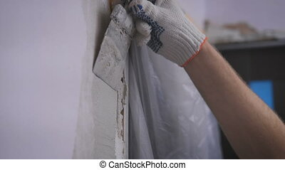 hand coating wall of plaster. Work gloves with a trowel in...