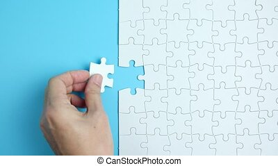 Hand putting the last piece of white jigsaw puzzle on blue background and place for your content