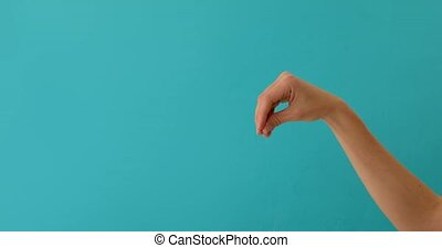 Chef hand adds salt to the dish, cooking falling liquid icooking food blue background