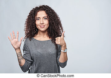 Hand counting - six fingers. Smiling woman showing six...