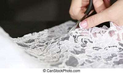 Hand cut white fabric with scissors of dressmaker cutting a ...