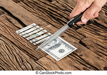 Hand Cutting The 100 Dollar Bill With Knife - Close-up Of...