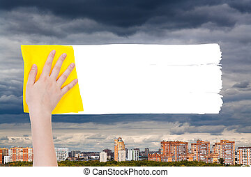 hand deletes rainy clouds over urban houses by rag