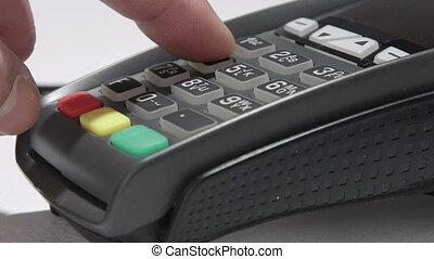 Hand dials the pin code into credit card reader