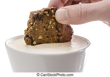 Hand dipping a cookie in cocoa