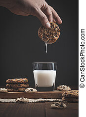 Hand dipping chocolate chip cookie in a glass of milk. on a wooden base, dark background. Sweet food concept.