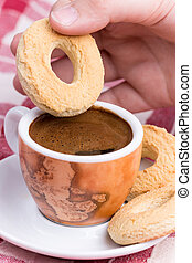 Hand dipping round cookie in to coffee cup