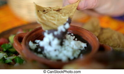 Hand slowly dipping tortilla chip into small clay bowl of black refried beans with cheese. Close-up of tasty beans, meat, and chopped vegetables with blurry background. Classic Mexican style meal