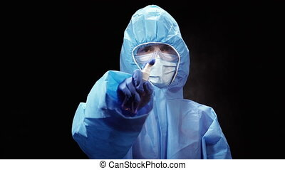 Hand disinfection. A woman in a protective antivirus suit ...