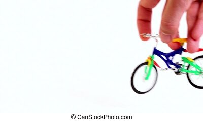 Hand does big jump trick on toy bike and leave, then repeats...