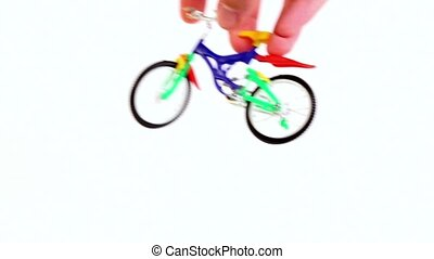 Hand does jump trick on toy bike and leave, then repeats...