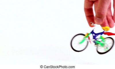 Hand does jump with slope trick on toy bicycle and leave, then repeats from other side
