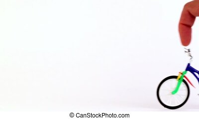 Hand does tricks on the toy bicycle, jump and rotate its...