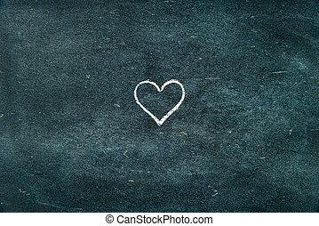 Hand drawing heart shape symbol on blackboard