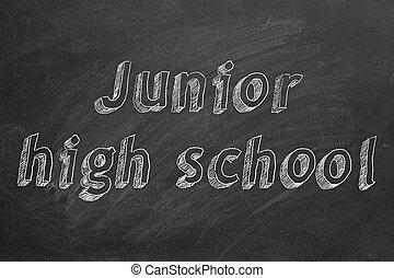 "Hand drawing ""Junior high school"" on black chalkboard"