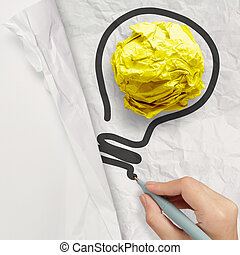 hand drawing light bulb on crumpled paper as creative concept