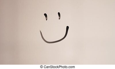 Hand drawing smiling face on glass. Hand drawing happy and sad smilies on glass