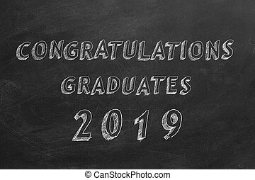"Hand drawing text ""Congratulations graduates. 2019."" on blackboard"