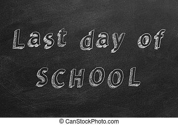 Hand drawing text `Last day of SCHOOL` on blackboard.