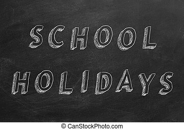 "Hand drawing text ""School holidays"" on blackboard."
