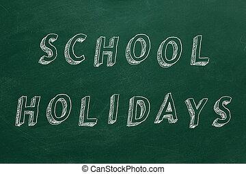 "Hand drawing text ""School holidays"" on green chalkboard."