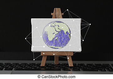 hand drawn globe with social network diagram on canvas and wooden easel on laptop computer as concept