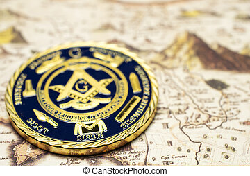 Hand drawn old vintage map of the fantasy land with mountains, castles, buildings, coastline and gold coin with masonic symbol on the map closeup view with selective focus.