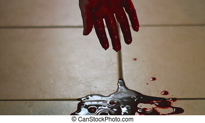 Hand dripping into blood pool on tile floor