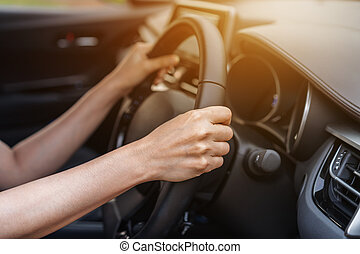 hand driving on steering wheel in car