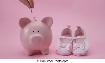 Hand dropping coin in piggy bank with baby booties in pink