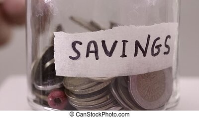 Hand Dropping Coins In A Saving Jar - Dropping Coins In A...