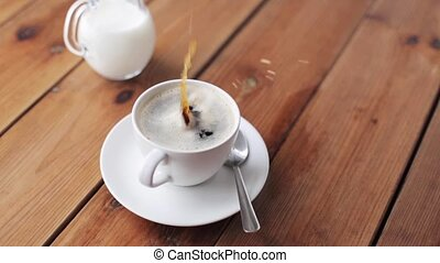 hand dropping sugar into coffee cup on table - unhealthy...