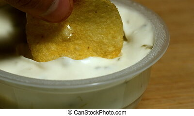 Hand dunking a chip into creamy dip in slow motion