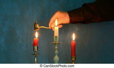 hand extinguish candlesticks and blue background