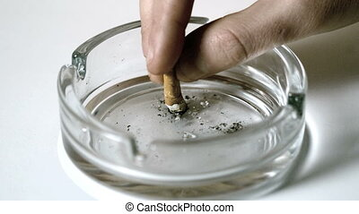 Hand extinguishing cigarette in empty ashtray in slow motion