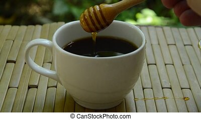 hand filling honey from wooden scoop in black coffee cup on...
