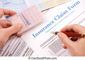 hand filling in insurance claim form
