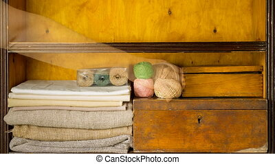 Hand fills shelves by materials and tools for needlework, embroidery and knitting. Vintage racks of handicraft studio with materials for handmade
