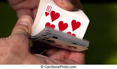 Hand flicking through deck of cards in slow motion