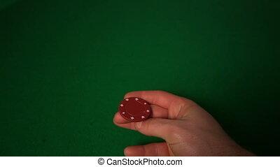 Hand flipping red casino chip