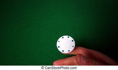 Hand flipping white casino chip in slow motion