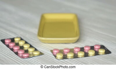 Hand folds tablets in container placed on a table