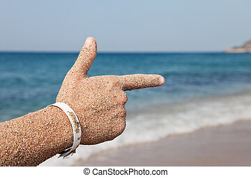 Hand forefinger pointing sea beach